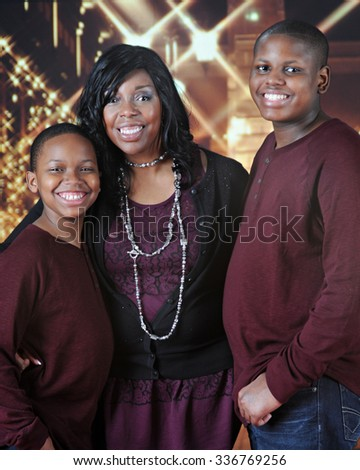 An attractive African American family happily standing outside a bright, Christmas-lit mall. - stock photo
