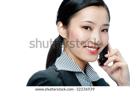 An attractive Asian businesswoman talking on phone against white background