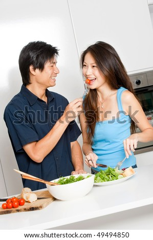 An attractive asian couple having a healthy salad in their kitchen at home - stock photo