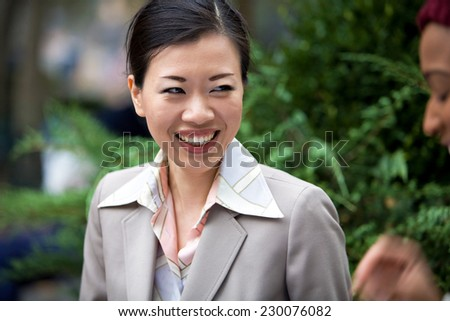An attractive Asian woman dressed in business attire laughing at the words of her business associate. - stock photo