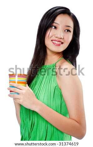 An attractive Asian woman in a green halter top with colourful cup on white background