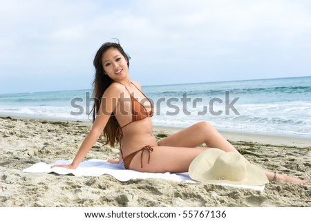 An attractive Asian woman relaxes at the beach while sunbathing during a beautiful day.