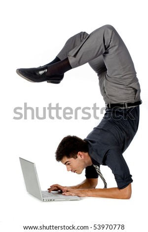 An attractive athletic businessman doing a handstand while using his laptop against white background - stock photo