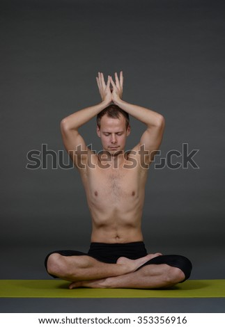 An attractive athletic man doing a yoga pose in studio on grey background.