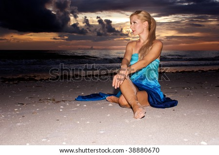 an attractive blonde woman with a ponytail is sitting on the beach at sunset, in profile with wrists crossed - stock photo