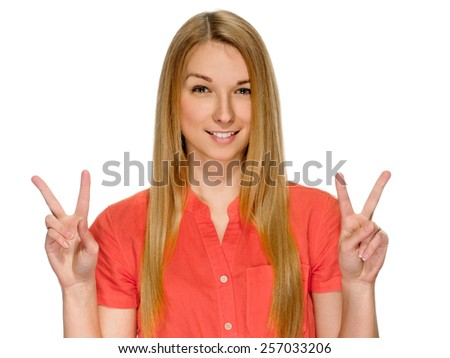 An attractive blonde young woman showing sign of victory on white background - stock photo