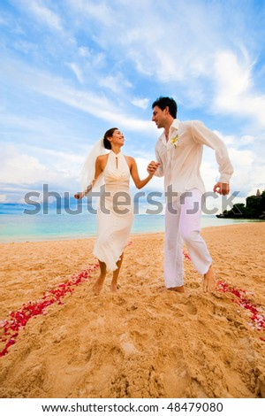 An attractive bride and groom getting married by the beach - stock photo