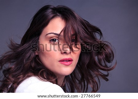 An attractive brunette woman flicking her hair - stock photo
