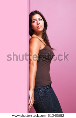 An attractive brunette woman in casual clothing leaning with her back against a wall in the corner of a room. Possible uses could include romance or listening related themes. - stock photo