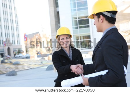 An attractive business construction team shaking hands on the building site - stock photo