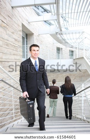 An attractive  business man walking up stairs at office building - stock photo