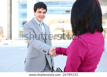 An attractive business team shaking hands at office building - stock photo