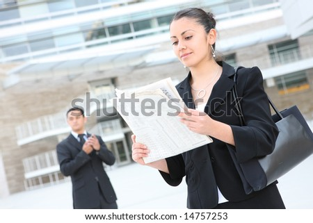 An attractive business woman reading the newspaper at office building - stock photo