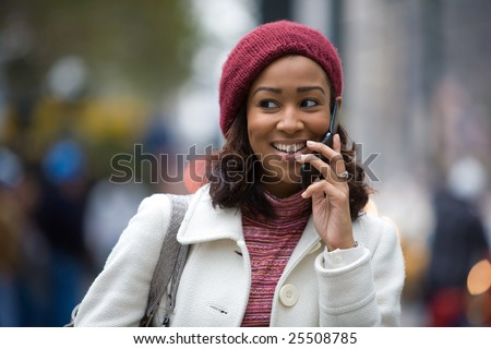 An attractive business woman talks on her cell phone as she walks through the city. - stock photo