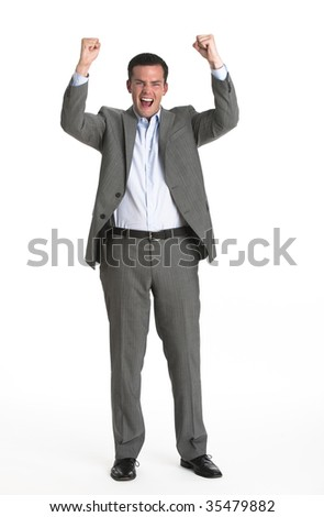 An attractive businessman cheering with his fists in the air.  Vertically framed shot.