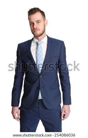 An attractive businessman wearing a blue suit and tie, standing in a studio with white background. - stock photo