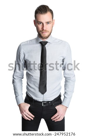 An attractive businessman wearing a grey shirt with a black tie, standing focused against a white background. Studio shot. - stock photo
