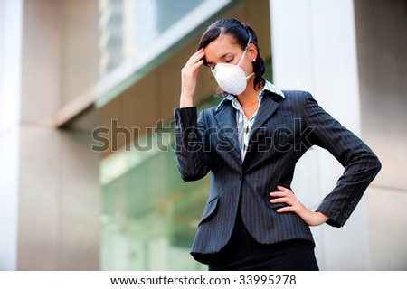 An attractive businesswoman wearing a mask to represent the state of the economy and world today - stock photo