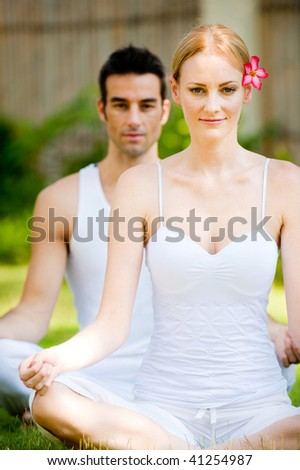 An attractive caucasian couple practicing yoga outdoors - stock photo