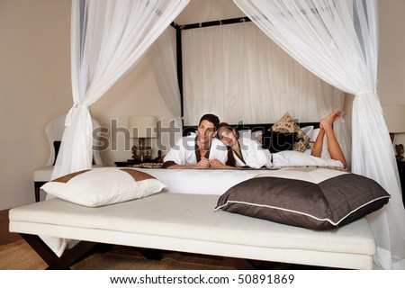 An attractive caucasian couple relaxing and lounging in their bedroom indoors - stock photo