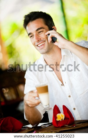 An attractive caucasian man with a drink and using his phone in a restaurant - stock photo