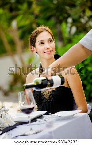 An attractive caucasian woman having red wine with her meal outdoors - stock photo