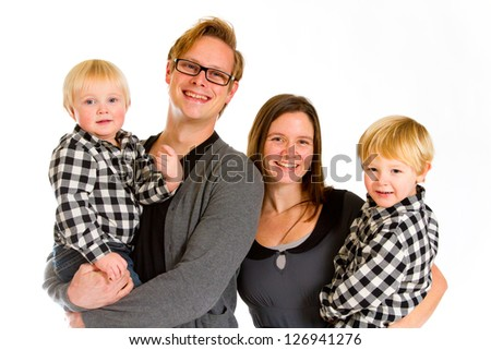 An attractive couple and their two sons against an isolated white background in the studio for a family portrait. - stock photo