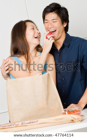 An attractive couple unpacking groceries in the kitchen at home - stock photo