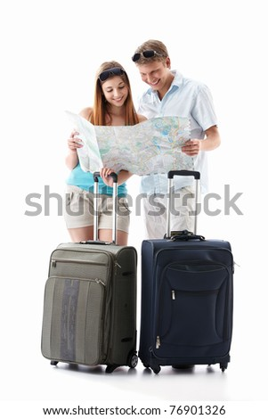 An attractive couple with their suitcases looking card is isolated - stock photo