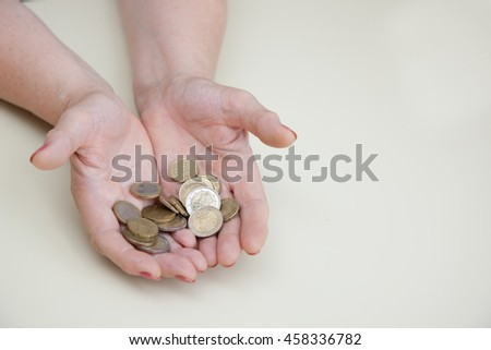 An attractive elderly woman pensioner counting money.WOMAN CONSIDERS RETIREMENT. MONEY IN THE HANDS OF WOMEN. Cash payments, pension funds.OLD WOMAN CONSIDERS COINS