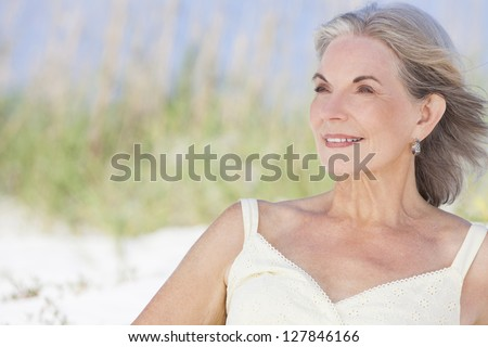 An attractive elegant classy senior woman in a yellow sun dress sitting on a white sand beach with grass and a blue sky behind her. - stock photo
