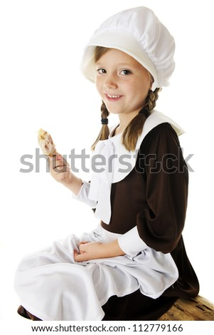 An attractive elementary Pilgrim girl enjoying a small drumstick as she sits on a log.  On a white background. - stock photo