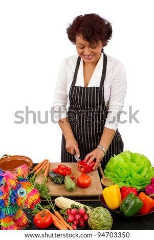 An attractive female chef preparing food for a Mexican celebration - stock photo