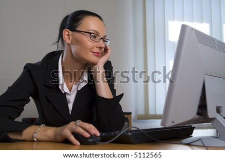 An attractive female executive happily working on her computer in the office