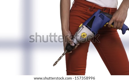 An attractive female holds a large electric power drill.