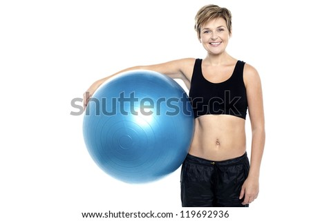 An attractive fit lady holding blue pilates ball isolated against white background - stock photo