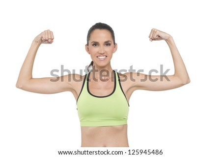An attractive, fit woman, wearing a sports bra flexes her muscles.