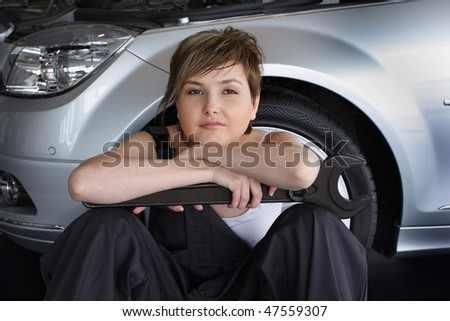 An attractive, friendly auto mechanic sitting with spanner wrench near the car