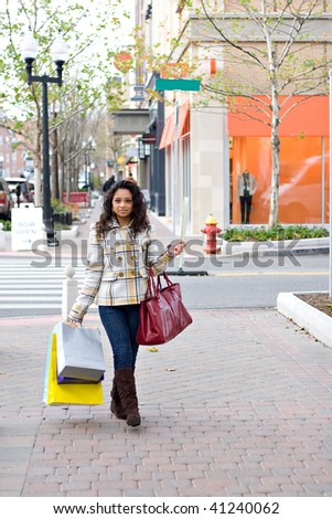 An attractive girl carrying a purse and shopping bags while enjoying a day in the city. - stock photo