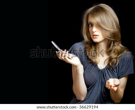 an attractive girl holding  mobile phone over a black background - stock photo