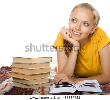 an attractive girl reading a book and dreaming - stock photo