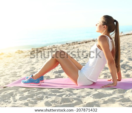 An attractive girl stretching before her workout. fitness athlete doing workout. - stock photo
