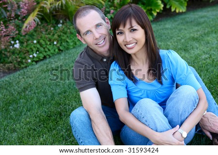 An attractive happy diverse couple in the park - stock photo