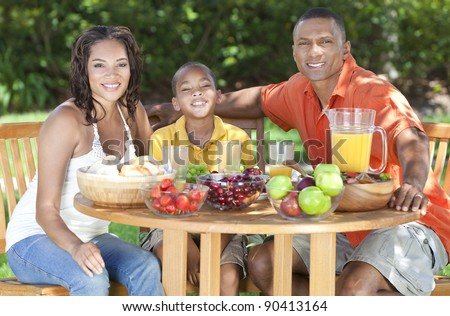 An attractive happy, smiling African American family of mother, father, son, man woman, boy child eating healthy food at a picnic table outside