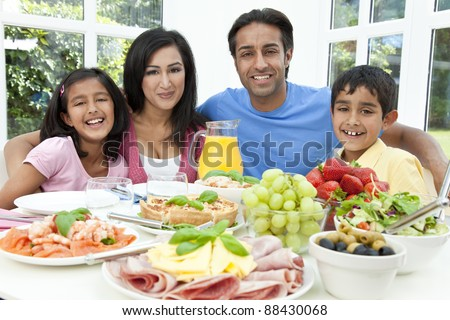 An attractive happy, smiling Asian Indian family of mother, father, son and daughter eating healthy food & salad at a dining table. - stock photo