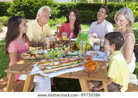 An attractive happy, smiling family of mother, father, grandparents, son and daughter eating healthy food at a picnic table outside - stock photo
