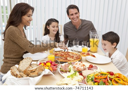 An attractive happy, smiling family of mother, father, son and daughter eating salad and pizza at a dining table, The mother is serving a slice of pizza to the excited boy.