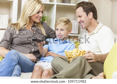 An attractive happy, young family of mother, father and son sitting on a sofa at home watching television the boy is using the remote control - stock photo