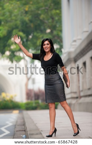An attractive Indian businesswoman outside waiting for a taxi cab