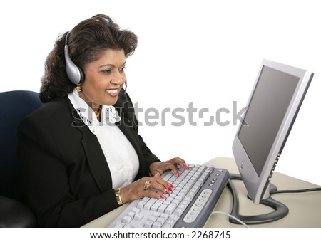 An attractive Indian technical support specialist sitting at the computer with a headset on.  Isolated on white. - stock photo